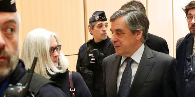 France's former Prime Minister Francois Fillon, right, and his wife Penelope, left, leave the Paris courthouse, in Paris, Monday, Feb. 24, 2020.