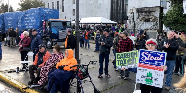 In this Feb. 6, 2020 file photo, demonstrators protest against a cap-and-trade bill aimed at stemming global warming protest at the Oregon State Capitol in Salem. Republican lawmakers on Monda boycotted the Oregon Senate in an effort to deny Democrats a quorum and doom a contentious climate change bill. (AP Photo/Andrew Selsky)