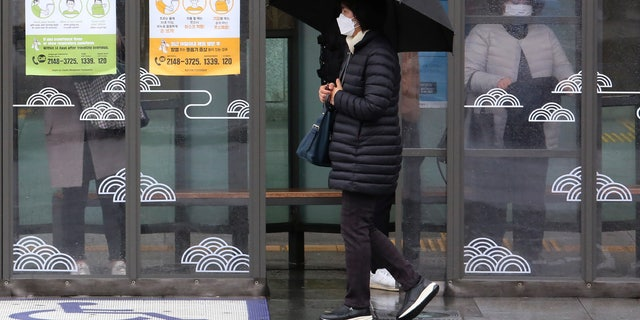 A woman wearing face mask passes by posters about precautions against new coronavirus at a bus station in Seoul, South Korea, Tuesday, Feb. 25, 2020. China and South Korea on Tuesday reported more cases of a new viral illness that has been concentrated in North Asia but is causing global worry as clusters grow in the Middle East and Europe. (AP Photo/Ahn Young-joon)