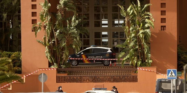 Spanish police officers stand outside the H10 Costa Adeje Palace hotel in Tenerife, on Tuesday, Feb. 25, 2020. Spanish officials say a tourist hotel on the Canary Island hotel of Tenerife has been placed in quarantine after an Italian doctor staying there tested positive for a new virus from China that has infected thousands worldwide.