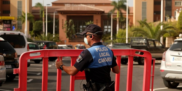 A Spanish police officer sets a barrier blocking access to the H10 Costa Adeje Palace hotel in Tenerife.