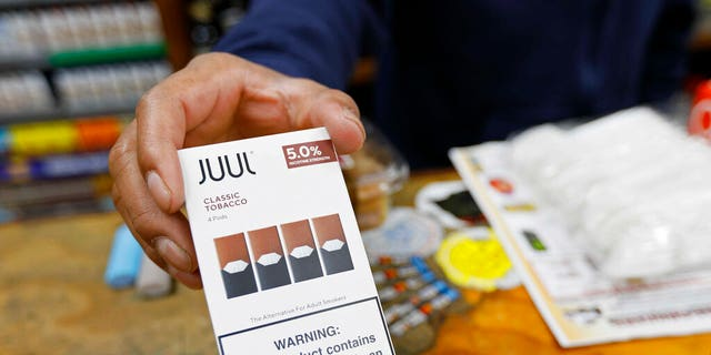 FILE: A cashier displays a packet of tobacco-flavored Juul pods at a store in San Francisco.