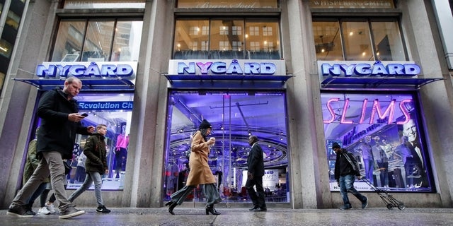Pedestrians pass the storefront of Peter Nygard's Times Square headquarters on Feb. 25. (AP Photo/John Minchillo)