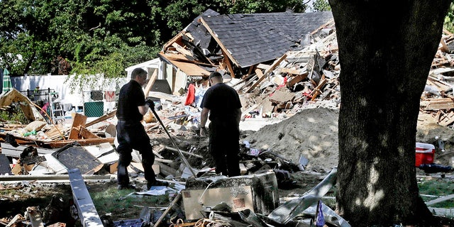 In this Sep. 21, 2018, file photo, fire investigators pause while searching the debris at a home which exploded following a gas line failure in Lawrence, Mass.