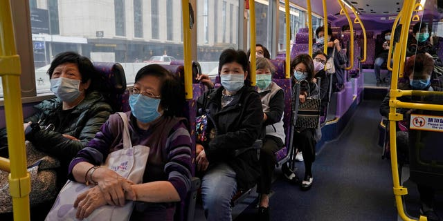 Passengers wears face masks as a precaution against the COVID-19 while sitting in a bus in Hong Kong, Thursday, Feb. 27, 2020.