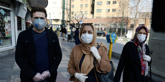 Tehran resident Leila Tayyeb, center, with her husband wearing mask and gloves, speaks with The Associated Press, as a woman walks past, in downtown Tehran, Iran, Thursday, Feb. 27, 2020.  (AP Photo/Vahid Salemi)