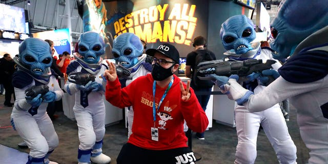 """Eric Vita, of Morris Plains, N.J., center, wears a protective mask while posing for a photograph with people dressed as """"Crypto,"""" the main character in the video game """"Destroy All Humans!,"""" Thursday, Feb. 27, 2020, at the Pax East conference, in Boston. Vita said concerns about the coronavirus played a role in his decision to wear a mask to the conference. (AP Photo/Steven Senne)"""