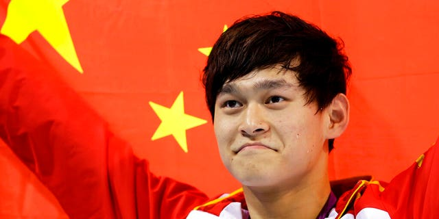 In this Saturday, Aug. 4, 2012 file photo, China's Sun Yang holds his national flag after winning the gold medal in the men's 1500-meter freestyle swimming final at the Aquatics Centre in the Olympic Park during the 2012 Summer Olympics in London. Chinese swimmer Sun Yang has been banned for eight years for breaking anti-doping rules and will miss the 2020 Tokyo Olympics.