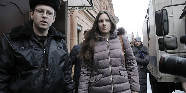 Alla Ilyina, who broke out of the hospital on Feb. 7 after learning that she would have to spend 14 days in isolation instead of the 24 hours doctors promised her, is escorted by a bailiff from a court after a session in St. Petersburg, Russia, on Monday.(AP)