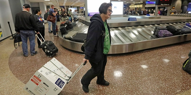 Ann Lovell carrying her box of prescriptions after returning to Salt Lake City International Airport following her visit to Tijuana, Mexico, last month. (AP Photo/Rick Bowmer, File)