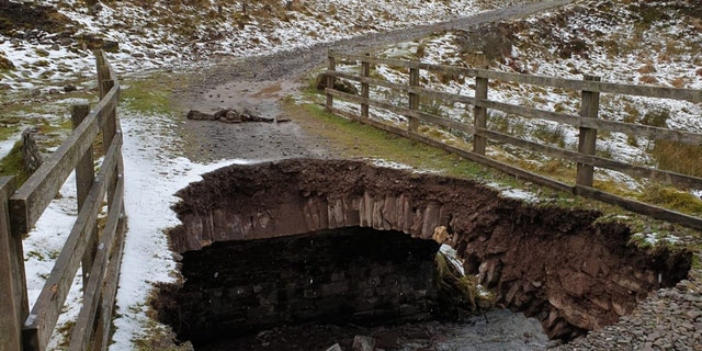 A large hole can be seen after part of a bridge collapsed at a national park in Wales on Wednesday.