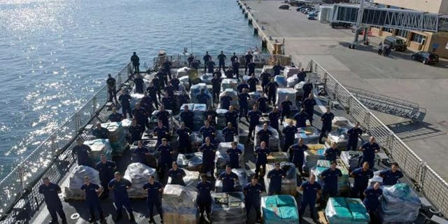 Members of the Coast Guard cutter Hamilton stand next to more than two dozens tons of cocaine.