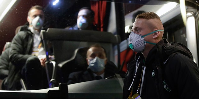 Bulgarian soccer team Ludogorets players, wearing protective face masks, get on a coach bus heading to the San Siro Stadium in Milan, Italy, Thursday, Feb. 27, 2020. (AP Photo/Luca Bruno)