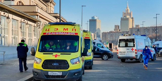 In this file photo taken on Friday, Feb. 21, 2020, Ambulance cars are parked while medics check passengers where a passenger was identified with suspected coronavirus after arriving from Kyiv at Kievsky rail station in Moscow, Russia.