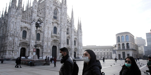 People wearing sanitary masks walk past the Duomo gothic cathedral in Milan, Italy, Sunday, Feb. 23, 2020.