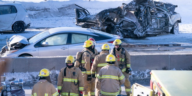 Emergency personnel stand next to demolished cars following a massive pileup involving numerous vehicles on the south shore of Montreal in La Prairie, Quebec, Wednesday, Feb. 19, 2020.