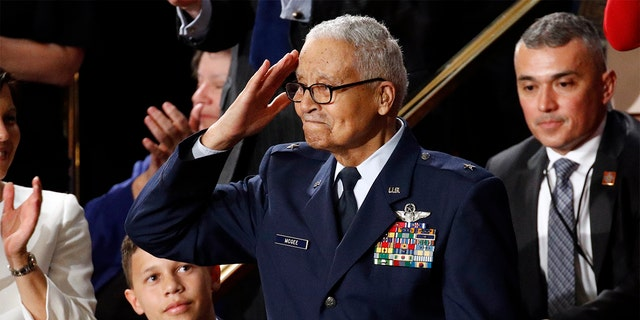 Tuskegee airman Charles McGee, 100, salutes as his great grandson Iain Lanphier looks as President Donald Trump delivers his State of the Union address to a joint session of Congress on Capitol Hill in Washington, Tuesday, Feb. 4, 2020. (AP Photo/Patrick Semansky)