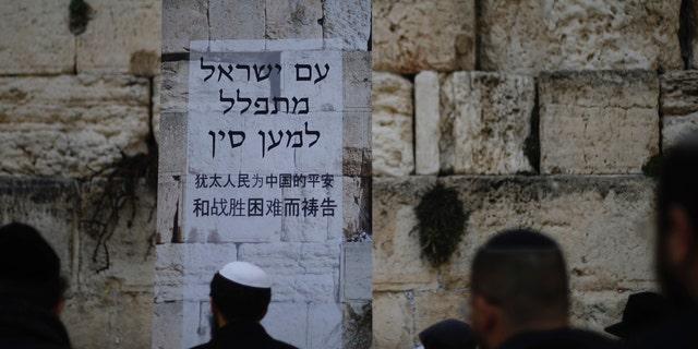"""Judeus rezam no Muro das Lamentações, o local mais sagrado onde os judeus podem rezar na Cidade Velha de Jerusalém, domingo, 16 de fevereiro de 2020. Enquanto as preocupações com a disseminação do coronavírus aumentam, os fiéis judeus realizaram uma sessão de oração domingo no Muro das Lamentações em busca do divino intervenção para ajudar a evitar doenças contagiosas. O pôster em hebraico e chinês diz: """"O povo de Israel ora pela China"""". (Foto AP / Ariel Schalit)"""