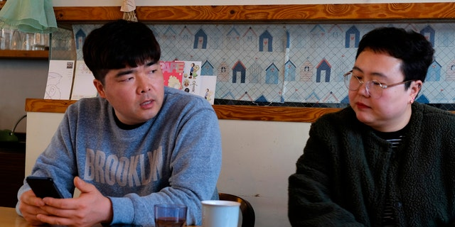 In this Wednesday, Feb. 19, 2020, photo, props manager Joo Dong-man, left, speaks as costume manager Yang Hee-hwa listens during an interview at a cafe in Ilsan, South Korea. (AP Photo/Juwon Park)