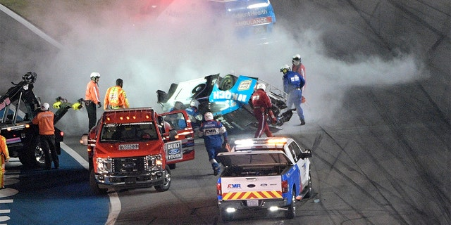 Track personnel arriving to help Ryan Newman (6) after he flipped his car on the final lap in front of the grandstands during NASCAR Daytona 500. (AP Photo/Phelan M. Ebenhack)