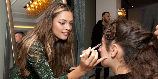"Demi-Leigh Nel-Peters puts makeup on one of the guests at the ""Night to Shine"" in Albania."