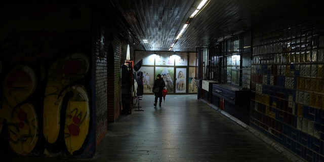 A woman walks through an underground passage during a rainy day in Belgrade, Serbia, Wednesday, Feb. 5, 2020. Weather forecasts predict changeable weather during the next few days.