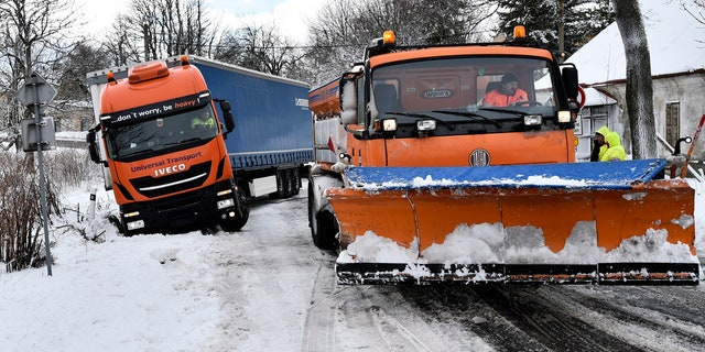 A snowplow pulls a truck stranded along a snow-covered road in the village of Naklerov, Czech Republic, Wednesday, Feb. 5, 2020.