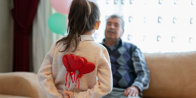 Cute little girl celebrating Valentine's day with parents, family and herself, holding heart shape decorations, home interior.