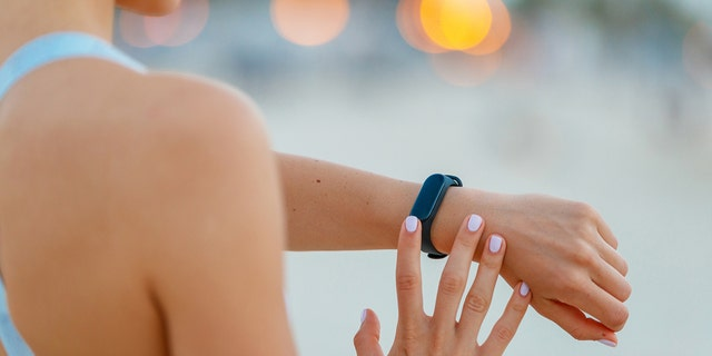Female jogger checking the fitness tracker on her wrist