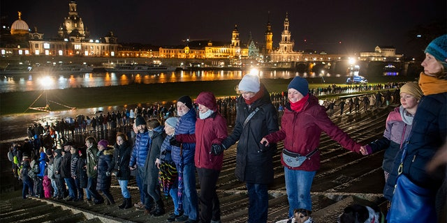 People form a human chain on the banks of the Elbe river with the historical old town in background, marking the 75th anniversary of the destruction of Dresden in the Second World War, in Dresden, Germany. (Robert Michael/dpa via AP)