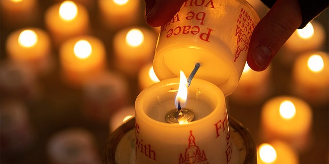 A child lights a candle in the Frauenkirche cathedral (Church of Our Lady) in Dresden, Germany. (AP Photo/Jens Meyer)