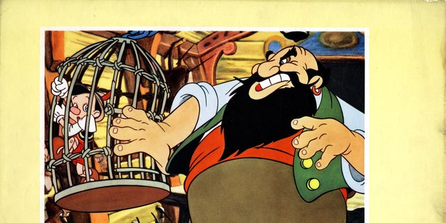 Pinocchio is trapped in Stromboli's cage. (Photo by LMPC via Getty Images)