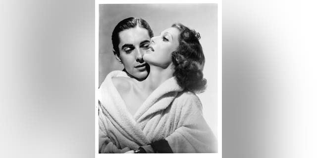 Tyrone Power holds Loretta Young in publicity portrait for the film 'Love Is News', 1937.
