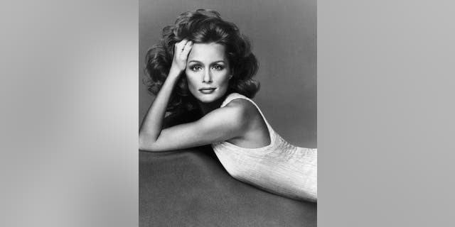 American actress and supermodel Lauren Hutton poses in a sleeveless dress in a pleated fabric, possibly by Mary McFadden, 1974.