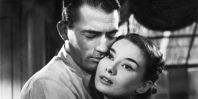 American actor Gregory Peck (1916 - 2003) and Belgian-born actress Audrey Hepburn (1929 - 1993) embrace in a still from director William Wyler's film, 'Roman Holiday'.