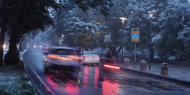 Fresh snow falls while motorists drive through Abu Nawas street in central Baghdad, Iraq, Tuesday, Feb. 11, 2020.