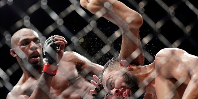 Jon Jones, left, delivering a kick to Dominick Reyes, right, during the bout at UFC 247 in Houston. (AP Photo/Michael Wyke)