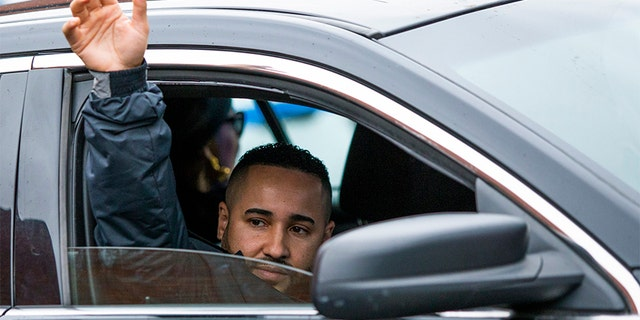 New York Police Department Lt. Jose Gautreaux, who was shot in the arm by a gunman who opened fire in a police precinct in the Bronx, waves to his colleagues as he is released from Lincoln Hospital in the Bronx on Monday.