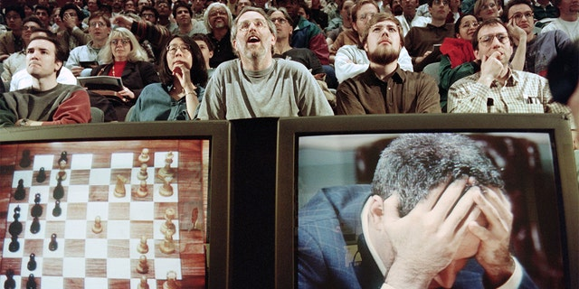 Chess enthusiasts watch World Chess champion Garry Kasparov on a television monitor as he holds his head in his hands at the start of the sixth and final match against IBM's Deep Blue computer in New York. Kasparov lost this match in just 19 moves giving overall victory to Deep Blue with a score of 2.5-3.5. / AFP / STAN HONDA (Photo credit should read STAN HONDA/AFP via Getty Images)
