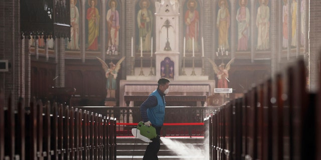 A worker wearing a face mask sprays disinfectant as a precaution against the new coronavirus at Myeongdong Cathedral in Seoul, South Korea, Wednesday, Feb. 26, 2020. (Lee Ji-eun/Yonhap via AP)