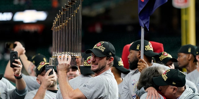 In this Oct. 30, 2019, file photo, Washington Nationals starting pitcher Max Scherzer celebrates with the trophy after Game 7 of the baseball World Series against the Houston Astros in Houston. The Nationals head to spring training with mostly the same squad that won the World Series. They are counting again on being led by a star-studded rotation featuring Scherzer and Stephen Strasburg, along with slugger Juan Soto. (AP Photo/David J. Phillip, File)