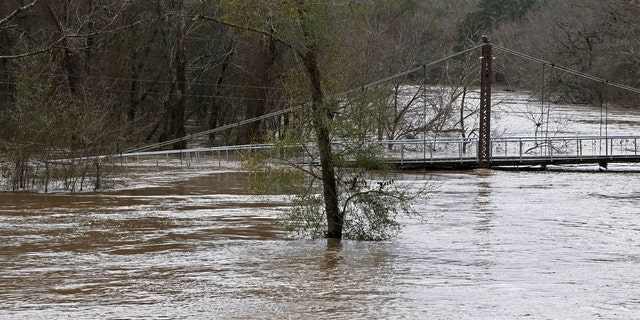 Water from the Pearl River floods Byram Swinging Bridge, which connects Hinds and Rankin Counties in Byram, Miss., Monday, Feb. 17, 2020.