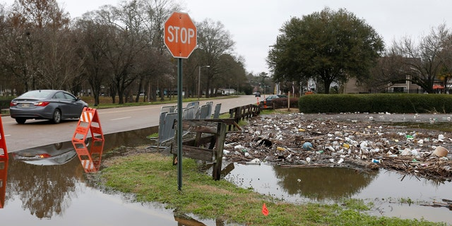 Trash and debris from the Pearl River floodwaters clog part of the Hanging Moss Creek Water in Jackson, Miss., Monday, Feb. 17, 2020.