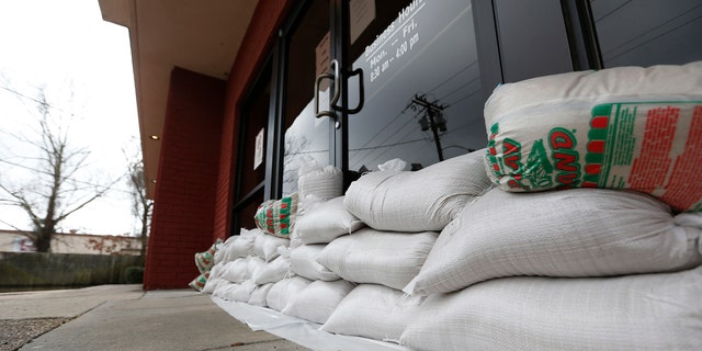 Sandbags protect the front of a credit union in downtown Jackson, Miss., as floodwaters from the Pearl River continue to rise in the Capital city., Monday, Feb. 17, 2020.