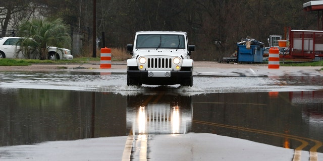 A vehicle carefully passes through a flooded street in downtown Jackson, Miss., as flooding from the Pearl River continues to impact several communities along its bank, Sunday, Feb. 16, 2020.