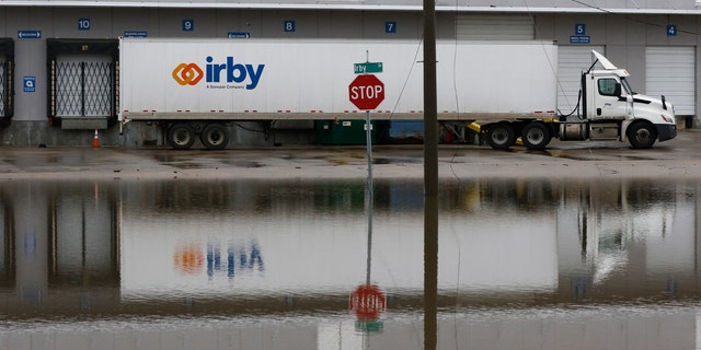 A parked tractor trailer's reflection is seen on a flooded street in downtown Jackson, Miss., as flooding from the Pearl River continues to impact several communities along its bank, Sunday, Feb. 16, 2020.