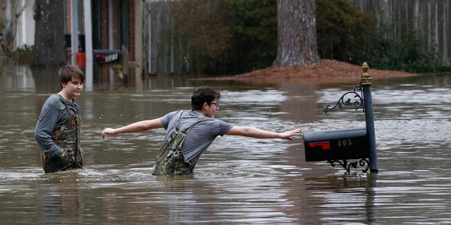 Blaine Henderson, right, reaches to tag a mailbox as Pearl River as he and his friend Jonah Valdez, both 12, play in the floodwaters of this northeast Jackson, Miss., neighborhood, Sunday, Feb. 16, 2020.