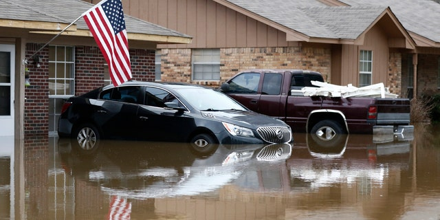 Abandoned vehicles are semi submerged in floodwater from the Pearl River in northeast Jackson, Miss., Sunday, Feb. 16, 2020.