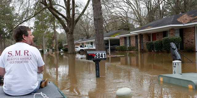 Chris Sharp studies the water damage from the Pearl River that floods his neighborhood in Jackson, Miss., Sunday, Feb. 16, 2020.