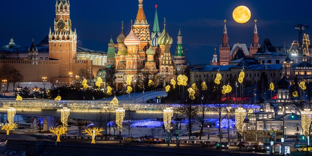 The full moon lights up the sky over the Moscow Kremlin waterfront, Spasskaya Tower, St Basil's Cathedral, on Feb. 8, 2020.